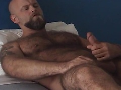 Watch Bear Troy play with his man meat on a bed!