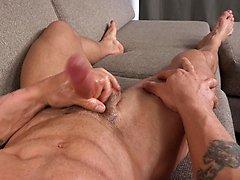 Muscled hunk Brennan strokes his dick